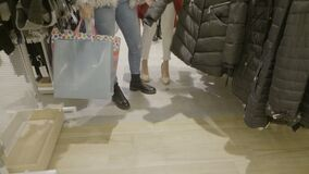 Close up of woman legs wearing a casual outfit walking and looking for clothes with shopping bags in their hands in mall store -. Close up of woman legs wearing stock footage