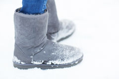 Close up of woman legs wearing warm boots on snow. People, footwear, winter and clothing concept - close up of woman legs wearing warm boots on snow Stock Photo