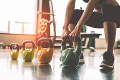 Close up of woman lifting kettlebell like dumbbells in fitness s. Port club gym training center with sport equipment near window background. Lifestyles and stock photo