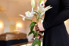 Close up of woman with lily flowers at funeral stock photography