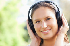 Close up of a woman listening to music in the park Stock Photos