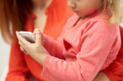 Close up of woman and little girl with smartphone Stock Photo