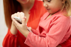 Close up of woman and little girl with smartphone Stock Photos