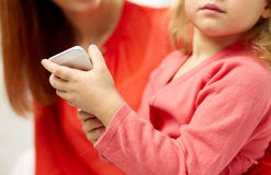 Close up of woman and little girl with smartphone Royalty Free Stock Images