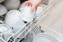 Close Up Of Woman Loading Crockery Into Dishwasher. Woman Loading Crockery Into Dishwasher Royalty Free Stock Photo