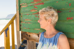 Close up of woman looking away while standing against wall. At beach Stock Photography