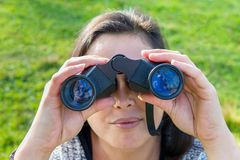 Close up woman looking through binoculars. Close up young woman looking through binoculars in nature Stock Images
