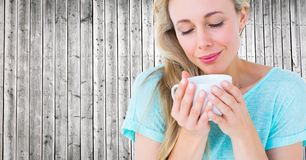 Close up of woman looking down at white cup against grey wood panel Stock Image