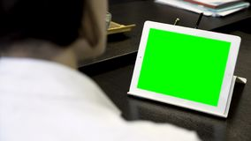 Close up for a woman looking at a white tablet with a green screen. Girl in white shirt working in office in front of stock image
