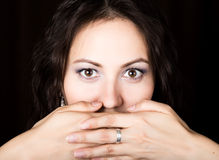 Close-up woman looks straight into the camera on a black background. She covered her mouth with her hand. expresses Stock Images