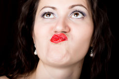 Close-up woman looks straight into the camera on a black background. expresses different emotions, sending a kiss Royalty Free Stock Photo