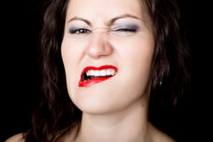 Close-up woman looks straight into the camera on a black background. expresses different emotions, showing teeth, biting Royalty Free Stock Image
