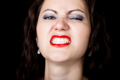 Close-up woman looks straight into the camera on a black background. expresses different emotions, showing teeth Royalty Free Stock Images