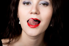 Close-up woman looks straight into the camera on a black background. expresses different emotions, showing tongue Royalty Free Stock Photos