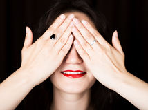 Close-up woman looks straight into the camera on a black background. laughing woman covering her eyes with her hand Stock Photo