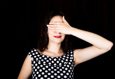 Close-up woman looks straight into the camera on a black background. laughing woman covering her eyes with her hand Royalty Free Stock Image