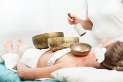 Woman receiving singing bell sound therapy. Close-up of a woman lying in spa with copper bowls receiving singing bell sound therapy stock photos