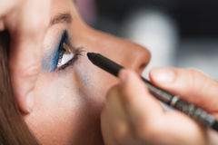 Applying eye makeup stock photography