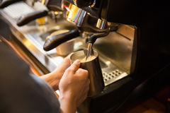 Close up of woman making coffee by machine at cafe Stock Photo