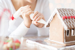 Close up of woman making gingerbread house at home Stock Image