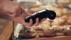 Close-up of woman making payment through NFC in bakery, cafe restaurant, mobile phone contactless pay for bill with Royalty Free Stock Photography