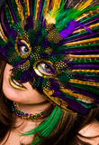 Close Up of Woman in Mardi Gras Mask. A portrait of a pretty woman with gold lips and a feather mask Stock Image