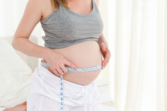 Close up of a woman measuring her belly Royalty Free Stock Photos