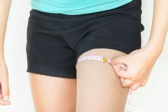 Close up of woman is measuring her thigh with measuring tape is. Olated on white background stock image