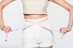 Close Up Woman measuring her waistline with measure line Stock Photos