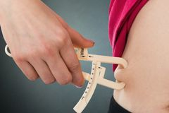 Woman Measuring Stomach Fat With Caliper. Close-up Of Woman Measuring Stomach Fat With Caliper Against Gray Background stock photography