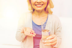 Close up of woman with medicine and water glass Stock Photo