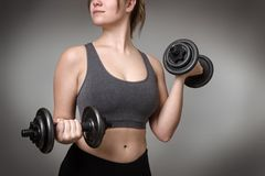 Fitness model on gray background. Close up of a woman middrifed using dumbbells Royalty Free Stock Image