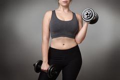 Fitness model on gray background. Close up of a woman middrifed using dumbbells Stock Photos