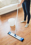 Close up of woman with mop cleaning floor at home Royalty Free Stock Photos