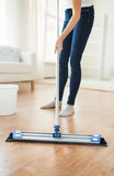 Close up of woman with mop cleaning floor at home Royalty Free Stock Images