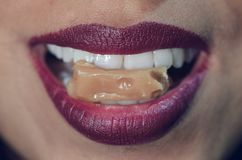 Close-up of woman mouth biting caramel candy royalty free stock image