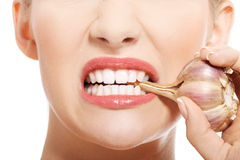 Close up on woman mouth with raw garlic. Stock Images