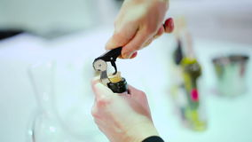 Close-up - woman open the wine bottle with corkscrew. Close-up. Woman`s hand holding a corkscrew and twist it in a wine bottle. The sommelier slowly pulling the stock footage