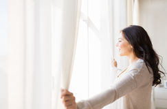 Close up of woman opening window curtains. People and hope concept - close up of happy woman opening window curtains Stock Photography