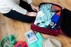 Close up of woman packing travel bag for vacation Royalty Free Stock Images