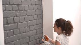 Close-up of a woman painting a brick wall in gray using a paint brush.