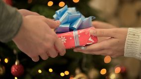 Close-up of woman passes gift to man. Close-up female gave his boyfriend Christmas or new year`s gift. Festive winter. Atmosphere stock photo