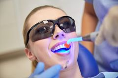 Close up of woman patient with dental curing light Stock Images