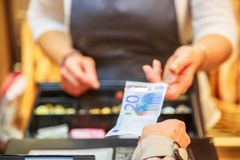 Woman is paying In cash with euro banknotes. Close up on woman is paying in a  bakery  with cash euro banknotes Stock Images