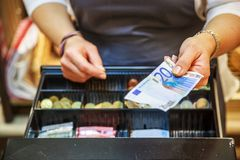 Woman is paying In cash with euro banknotes. Close up on woman is paying in a  bakery  with cash euro banknotes Stock Photo