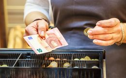 Woman is paying In cash with euro banknotes. Close up on woman is paying in a bakery with cash euro banknotes and coin Royalty Free Stock Photos
