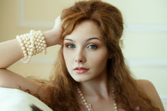 Close-up woman with pearls. Close-up red-haired woman with a pearls bracelet Royalty Free Stock Photo