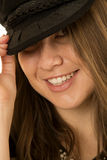 Close-up of a woman peering playfully wearing black hat Royalty Free Stock Image