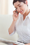 Close up of a woman with a phone and a newspaper Stock Images