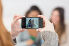 Close up of a woman photographing friends with smartphone Royalty Free Stock Image